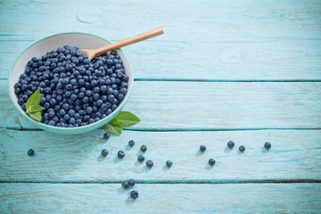 blueberries in plate on old wooden background
