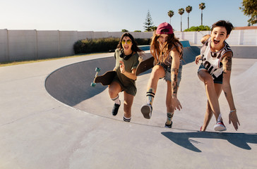 Laughing women climbing a skateboard ramp