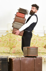 Macho, elegant porter on strict face carries pile of vintage suitcases. Man with beard and mustache wearing classic suit delivers luggage, luxury white interior background. Butler and service concept.