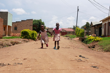 Twin sisters Nakato Rahian and Babirye Sumayia, who were kidnapped and later rescued by Uganda police, play near their home in Luwero town