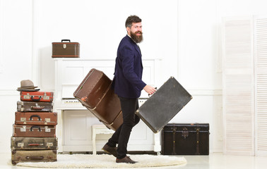 Butler and service concept. Macho attractive, elegant on smiling face carries vintage suitcases. Man with beard and mustache wearing classic suit delivers luggage, luxury white interior background.