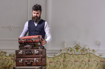 Man, traveller with beard and mustache packing luggage before trip, luxury interior background. Macho elegant on thoughtful face standing near pile of vintage suitcase. Luggage and travelling concept.