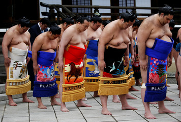 Sumo wrestlers pray during a ritual ceremony at the start of an annual sumo tournament dedicated to the Yasukuni Shrine in Tokyo