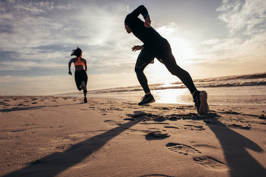 Fit people sprinting on the beach