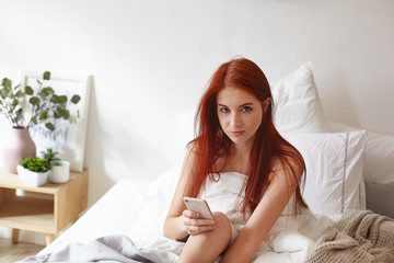 Picture of positive pretty girl with ginger hair and freckles skin sitting in bedroom, wrapped in white blanket, messaging online with friend via social networks or messengers using mobile phone