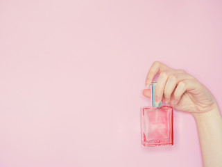 beauty for woman concept from beauty woman hand show and hold perfume bottle in hand with isolated pink pastel background