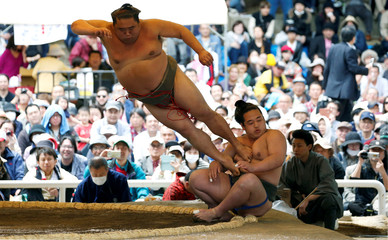 Sumo wrestlers perform a show fight during an annual sumo tournament dedicated to the Yasukuni Shrine in Tokyo