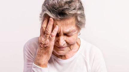 Studio portrait of a senior woman in pain. Close up.