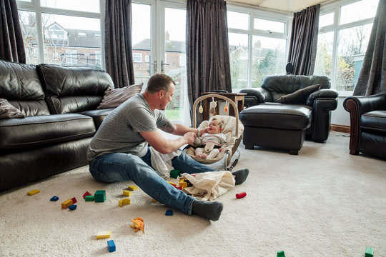 Father Relaxing at Home with his Baby Daughter