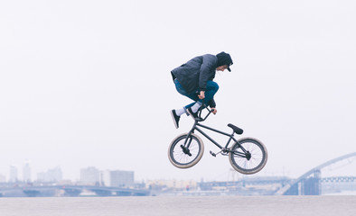 A young man makes a TAilwhip trick in the air on a BMX bike. BMX trick against the backdrop of urban minimalist landscape. BMX freestyle