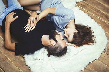 Heterosexual couple young beautiful man and woman on wooden floor background