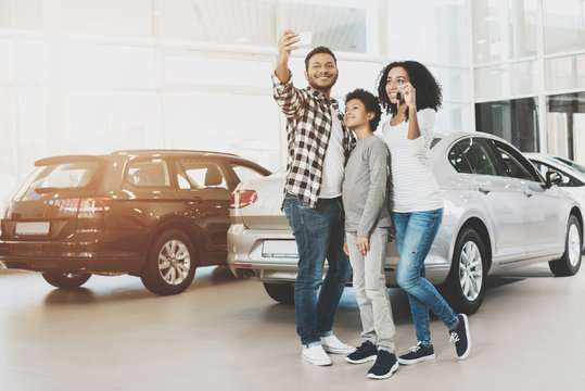 African american family at car dealership. Mother, father and son are taking selfie in front of new car.
