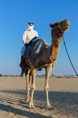 Arab man riding a camel in the desert