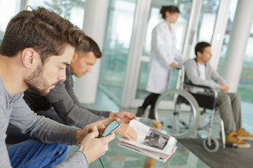 Man using smartphone in hospital waiting area