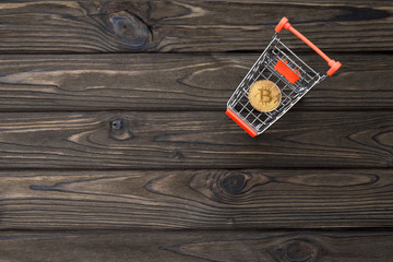 a cart from a supermarket, bitcoin on a wooden background. virtual money. the Internet