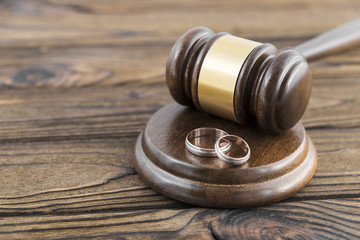 hammer of a judge, a pair of wedding rings on a wooden background. family law. divorce. marriage contract