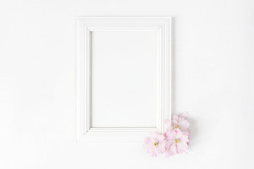 White blank wooden picture frame mockup with pink Japanese cherry blossoms lying on the white table. Poster product design. Styled stock feminine photography. Home decor. Spring concept.