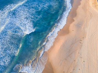 Aerial view of clean coastline under morning golden light. Wall mural