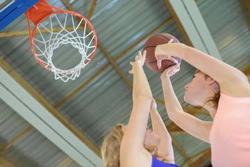 Women plaing basketball, aiming for hoop