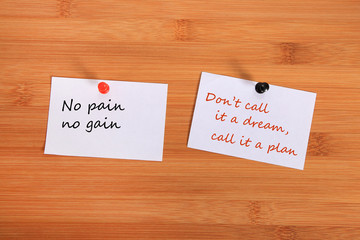 """""""No pain no gain."""" """"Don't call it a dream, call it a plan"""".  Note pin on the bulletin board."""