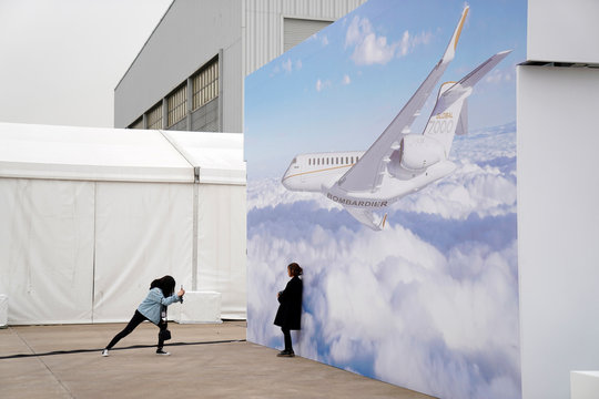 Women take picture in front of a billboard poster of the Bombardier Global 7000 aircraft at the Asian Business Aviation Conference and Exhibition at Hongqiao International Airport in Shanghai