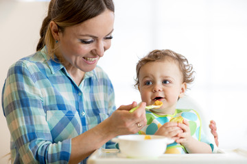smiling baby boy eating food with mom on kitchen