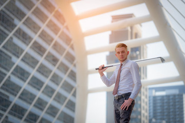 Portrait of Young businessman playing Golf on blurred city background.