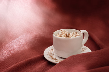 Hot sweet cocoa drink with marshmallow, bright sun light, textured textile background with copy space.