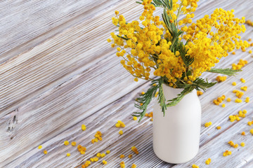 Vase with mimosa on old wooden background. Bunch of yellow fluffy flowers acacia in white ceramic vase is rustic still life. Selective focus.
