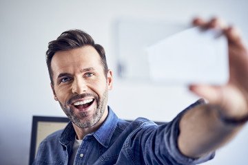 Happy man in office taking selfie