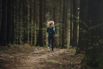 Fototapeta Young fitness woman running in the forest trail obraz