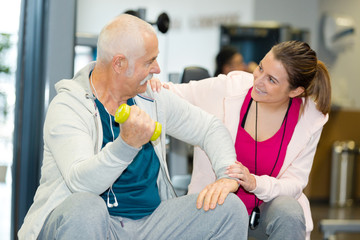 senior man exercising in gym with young instructor