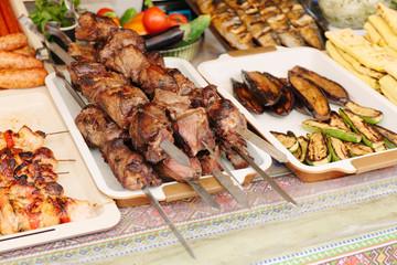Grilled kebab on metal skewer. Showcase of street food.