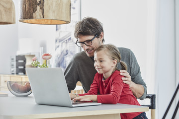 Smiling father and daughter using laptop on table at home