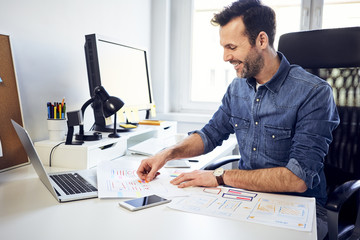 Smiling web designer working on draft at desk in office