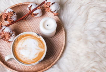 Coffee and candle on the wooden tray