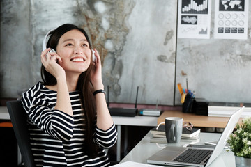 Young asian woman wearing headphones smiling with happiness while working, work at home, casual office life concept