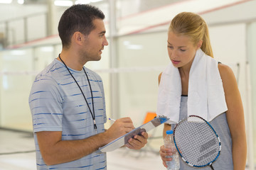 coach talking to female tennis player