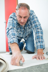 middle-age craftsman cutting carpet with cutter