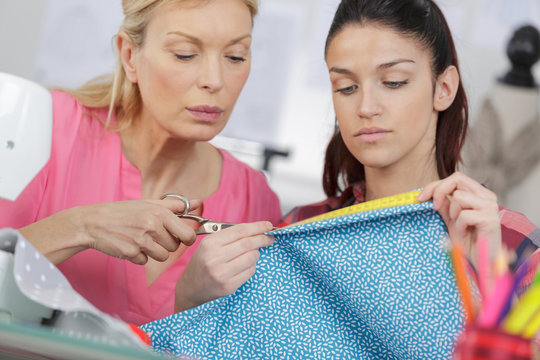 teacher helping student studying fashion and design