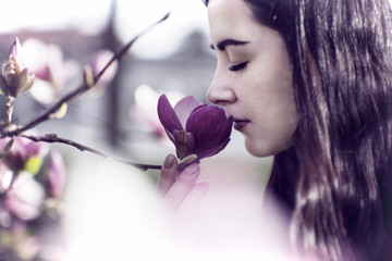 Beautiful girl smelling the flowers. Blossoming magnolia in the park garden.