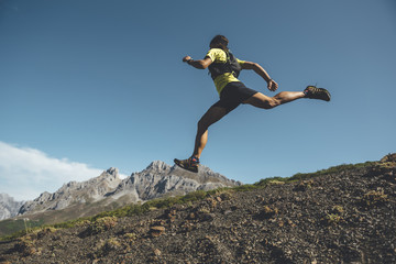 Trail runner jumping downhill in Picos de Europa Natural Park, Asturias, Spain