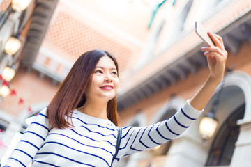 Young attractive asian woman taking her selfie with her smart phone at an outdoor shopping mall