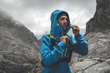 Portrait of a backpaker wearing a hooded jacket on a rainy day in Picos de Europa Natural Park, Asturias, Spain