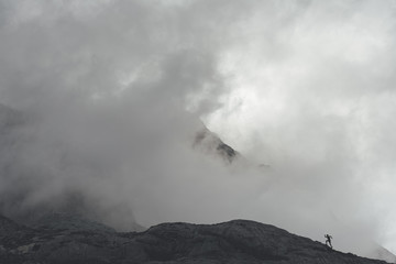 Silhouette of a trail runner running  uphill in Picos de Europa Natural Park on a foggy day, Asturias, Spain