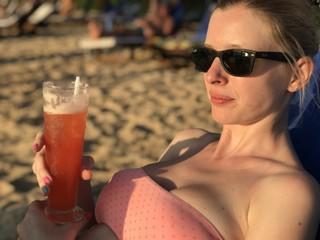 Jeune femme blonde dégustant un cocktail sur la plage en bikini rose