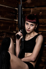 Beautiful sexy redhead holding pneumatic weapon on a wooden background
