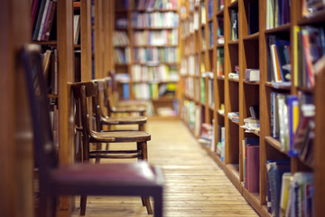 Library with books on shelf and empty chairs