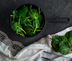resh green spinach in a round cast-iron frying pan