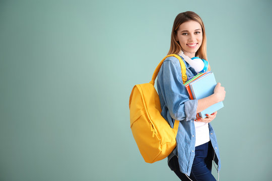 Pretty student with notebooks on color background